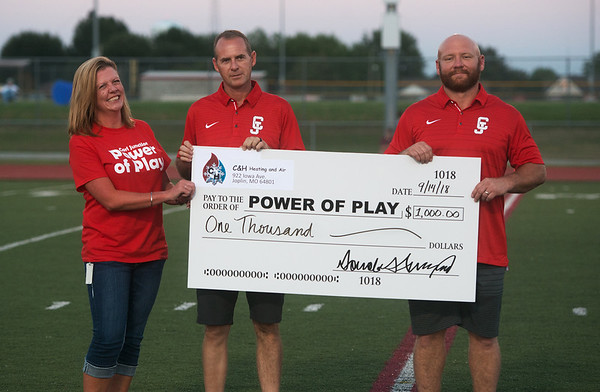 (from left) Heather Linscheid, occupational therapist for the Carl Junction School District, accepts a check from Dustin Coleman and Frank Huffman, owners of C&H Heating and Air for the Power of Play initiative during Friday's football game in Carl Junction. Power of Play is collecting funds to renovate a Carl Junction school playground to make it accessible for those with disabilities and special needs.<br /> Globe | Roger Nomer