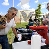 From the left: Joe Adams gets a cool cup of water for his puppy, Sammy Adams as Jessica Gibson volunteers at the Kiwanis beverage tent during the Joplin Arts Fest on Saturday at Mercy Park.<br /> Globe | Laurie Sisk