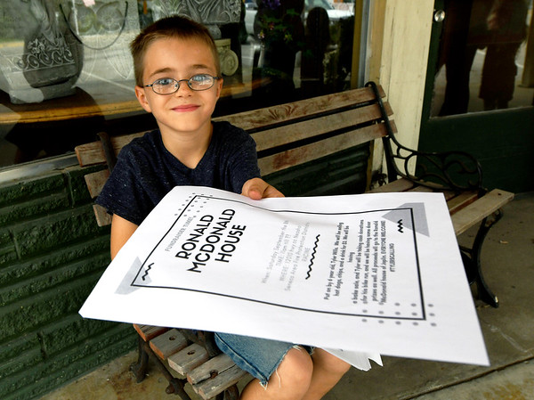 Six-year-old Tyler Wills, of Seneca, holds a flier he is using to publicize a fundraiser for the Ronald McDonald House as he sits on a storfront bench in downtown Seneca on Wednesday.<br /> Globe | Laurie Sisk