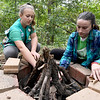 From the left: Girl Scouts Emily Graves, 11 and Shayla Gould, 12, demonstrate to younger scouts how to build a fire on Wednesday at Camp Mintahama.<br /> Globe | Laurie Sisk