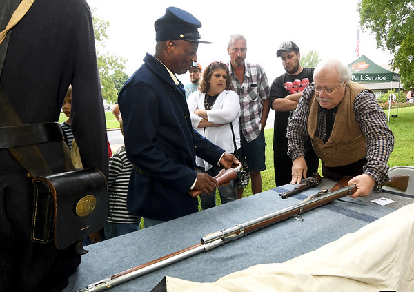 Ogis Davis, left, represents a soldier from the 1st Kansas Colored Infantry as Steve Weldon, right, of the Sherwood/Rader Farm Civil War Park, discusses some of the weapons used during the Civil War era on Saturday at George Washington Carver National Monument's Prairie Day.<br /> Globe | Laurie Sisk