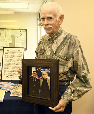 On Monday, local artist Larry Glaze holds a photo of himself and FDNY Firefighter Paulie Johnson, which is part of a display of artifacts and memorabilia at SMB Bank on North Main Street from the Sept. 11, 2001 attacks on the World Trade Center. The display includes a metal scrap from one of the twin towers and numerous photographs of the first squad of firefighters to arrive on the scene.<br /> Globe | Laurie Sisk