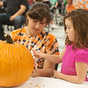 Layla Whittenburg, 6, Webb City, helps Sasha Norman carve a pumpkin on Wednesday at the Joplin Public Library.<br /> Globe | Roger Nomer