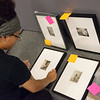 Shay Thomas, a Missouri Southern senior from El Dorado Springs, sets up a gallery of photos by Edvard Munch at the Spiva Gallery at MSSU on Wednesday.<br /> Globe | Roger Nomer
