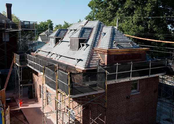 The roof of the Schifferdecker carriage house is undergoing restoration on Wednesday.<br /> Globe | Roger Nomer