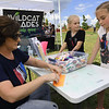 From the left: Eden Elliott, of the Spiva Center for the Arts, assists Melissa Jordon, 9 and Kate Jordon, 7, as they create custom decorated accordian fans at the Joplin Arts Fest on Saturday at Mercy Park.<br /> Globe | Laurie Sisk