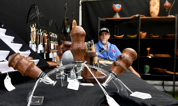 Dan McKInzie, of Republic, mans his booth behind a handcrafted set of bottle stoppers during the Joplin Arts Fest on Saturday at Mercy Park.<br /> Globe | Laurie Sisk