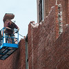 A worker removes bricks from the Howsmon building on Thursday.<br /> Globe | Roger Nomer