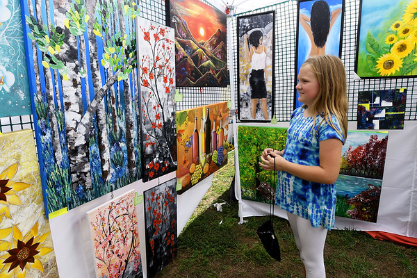 Ten-year-old Peyton Thornton checks out the colorful paintings of Overland Park artist Angela Alec during the Joplin Arts Fest on Saturday at Mercy Park.<br /> Globe   Laurie Sisk