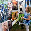 Ten-year-old Peyton Thornton checks out the colorful paintings of Overland Park artist Angela Alec during the Joplin Arts Fest on Saturday at Mercy Park.<br /> Globe | Laurie Sisk