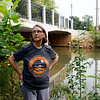 Rebecca Jim, executive director of the LEAD Agency, talks about the future of Tar Creek in Miami on Monday. Orange marks on the bridge and rocks in the background mark pollution from the river.<br /> Globe | Roger Nomer