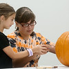 Mirabella Moore, 8, Joplin, helps Sarah Norman carve a pumpkin on Wednesday at the Joplin Public Library.<br /> Globe | Roger Nomer