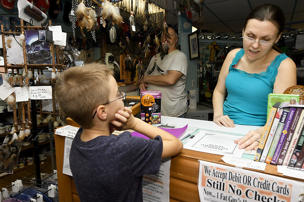 Six-year-old Tyler Wills, of Seneca, pitches his fundraiser for the Ronald McDonald House to 1 Fat Guys Flea Markey owner Lar Dee Benson and his wife Jennifer Benson in downtown Seneca on Wednesday.<br /> Globe | Laurie Sisk