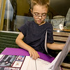 Six-year-old Tyler Wills, of Seneca, organizes a folder with publicity for two different events as he sits on a storefront bench in downtown Seneca on Wednesday.<br /> Globe | Laurie Sisk