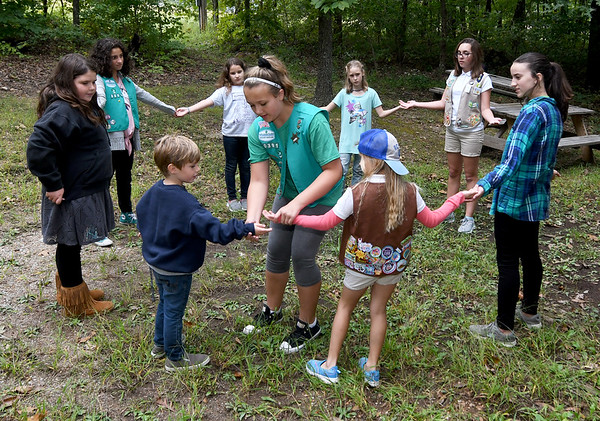 Girl Scout Emily Graves, center, assists other scouts and Troop 70391 mascot Owen Wiliams, 5, during a game of Quack-diddily-elbow on Wednesday at Camp Mintahama.<br /> Globe | Laurie Sisk