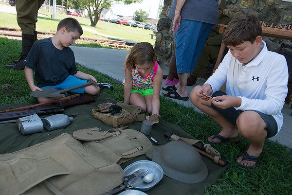(from left) John Marshall Channel, 6, Rachel Channel, 9, and Michael Peters, 10, check out World War I infantry items on display at King Jack Park in Webb City on Saturday.<br /> Globe | Roger Nomer