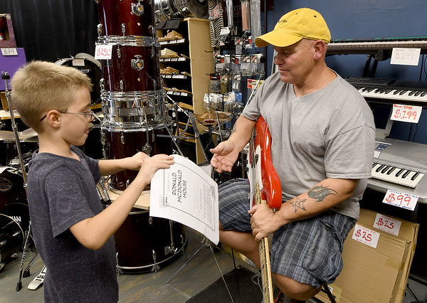 From the left: Six-year-old Tyler Wills, of Seneca, hands a flier he is using to publicize a fundraiser for the Ronald McDonald House to Chad Emmert, owner of G-Strings and F-Holes Music in downtown Seneca on Wednesday.<br /> Globe | Laurie Sisk
