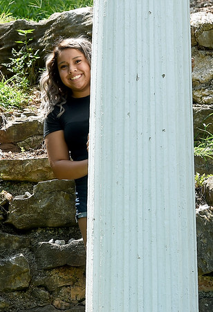 """Arely Avitua stands in behind a column at Big Spring Park in Neosho on Wednesday. Avitua recently was the youngest cast member of the MTV-produced reality show, """"The Real World.""""<br /> Globe 