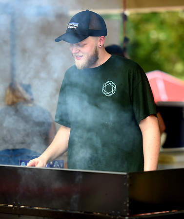 Caleb Heinlein, youth minister at St. Paul's United Metodist Church, braves the smoke and heat as he grills food as a fundraiser for the church;s youth programs during the Carl Junction Bluegrass Festival on Saturday at Center Creek Park. <br /> Globe | Laurie Sisk