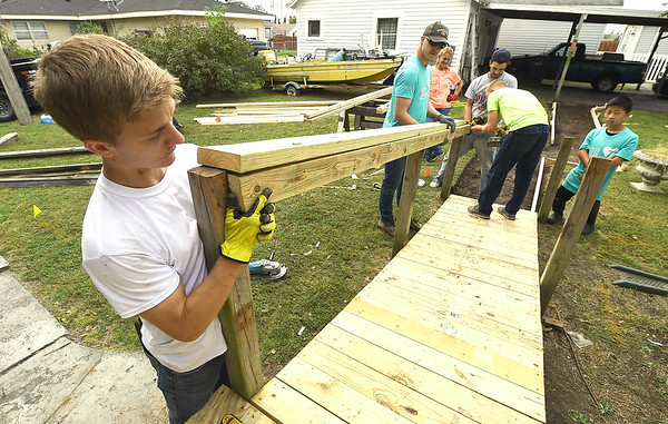 From the left: Hearts and Hammers volunteers Corbin Bandy, Trey Laveroni, Kacy Burks, Wade Liska, Caiton Bundy and Max Hunt install handrails on a ramp at a Webb City home on Main Street on Saturday. About 155 volunteers from God's Resort, Hearts & Hammers and Joplin Area Habitat for Humanity tackled 22 projects as part of a Brush With Kindness event.<br /> Globe | Laurie Sisk