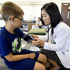 Kansas City University student Janet Han check's eight-year-old Elyy Vincent's blood pressure during KCU's Score 1 for Health event on Tuesday at KCU. The children's preventative screening program involved about 130 West Central Elementary students and included basic health screenings and educational presentations for the kids.<br /> Globe | Laurie Sisk