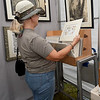 Loretta Moss, of Neosho, checks out the work of Ozark artist David Bigelow during the Joplin Arts Fest on Saturday at Mercy Park.<br /> Globe | Laurie Sisk