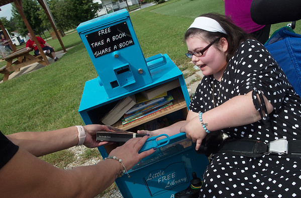 Chrissy Keeling helps stock a Little Free Library at Community Support Services of Missouri after a ribbon cutting for the library on Tuesday. Keeling helped create the lending library because she has always wanted to be a librarian, and wanted to share the value of reading with the community.<br /> Globe | Roger Nomer