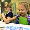 Seven-year-old Addi DiToro unleashes her inner artist as Aubree Williams, 10 looks on during Creation Station on Tuesday afternoon at the Spiva Center for the Arts. The class was the second of the school year for young artitsts to explore their creativity.<br /> Globe | Laurie Sisk
