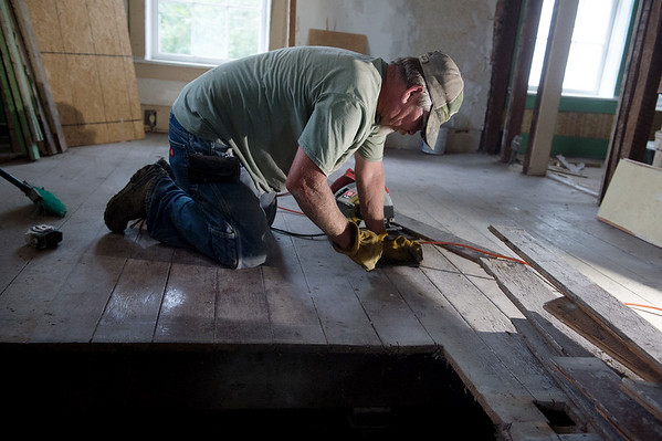 Terry Beetem works on repairs to the floor of the Sweet House on Tuesday in Carthage.<br /> Globe | Roger Nomer