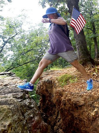 "Volunteer hiker Becky Browne leaps over Mother Nature's Crack during the ""Let's Roll '19 Ruck March"" on Saturday. The event, sponsored by Compass Quest, included about 30 participants who hiked the 14-mile course to raise awareness concerning veteran's issues.<br /> Globe 