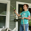 Sixteen-year-old Andrew Roberts clean the front porch of a Webb City home on Ball Street on Saturday. About 155 volunteers from God's Resort, Hearts & Hammers and Joplin Area Habitat for Humanity tackled 22 projects as part of a Brush With Kindness event.<br /> Globe | Laurie Sisk