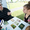 From the left: Lauren Woodal gives a tarot card reading for Holly McMullin at Mama Gaia's of Springfield's booth at the Pagan Pride Day on Saturday at Cunningham Park. The event featured crafts, homemade products and fellowship for those who chose to practice alternative beliefs.<br /> Globe | Laurie Sisk