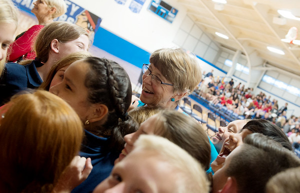 Sister Joan Schwager gets a group hug from St. Mary's Elementary fifth-grade students during a surprise celebration marking her 50-year service with the Sisters of Mercy at McAuley High School on Friday. Currently, she teaches religion at St. Mary's and St. Peter's Middle School.<br /> Globe | Roger Nomer