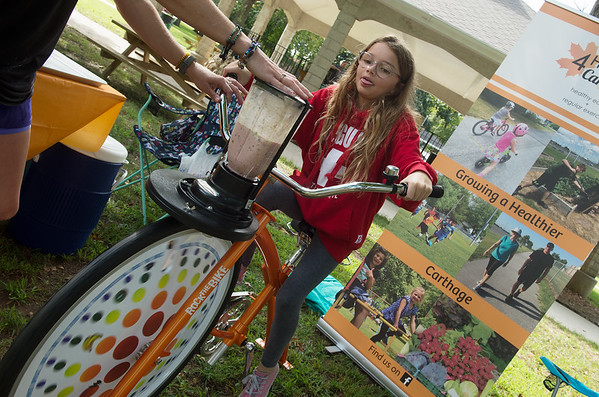 Brooke Gaddis, 10, pedals hard on smoothie bike as she makes a smoothie on Friday at the HERE 4 Carthage booth at Food Truck Friday in Carthage's Central Park.<br /> Globe | Roger Nomer