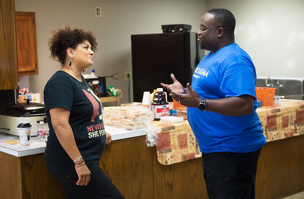 Nanda Nunnelly, president of the Community Service Center board, talks with Larry Fennell during a service project by members of the Phi Beta Sigma Fraternity on Friday at the center.<br /> Globe | Roger Nomer