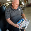 Bobby Ballard displays a binder full of his racing bibs during an interview on Monday.<br /> Globe | Roger Nomer