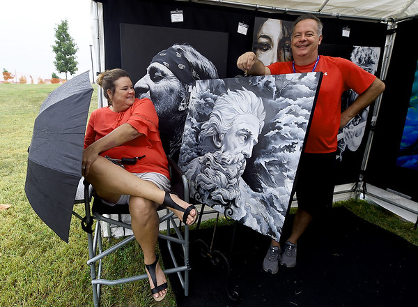 From the left: Angela Vanslyke uses an umbrella to shield her husband Matt Vanslyke's paintings from the rain during the Joplin Arts Fest on Saturday at Mercy Park. The Bella Vista , Ark. couple were among the scores of artists exhibiting their work on Saturday at the event.<br /> Globe | Laurie Sisk