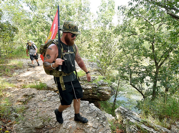 "Compass Quest trainer Matt Hay leads a group of volunteers as hike on the bluffs overlooking Shoal Creek during the ""Let's Roll '19 Ruck March"" on Saturday. The event, sponsored by Compass Quest, included about 30 participants who hiked the 14-mile course to raise awareness concerning veteran's issues.<br /> Globe 