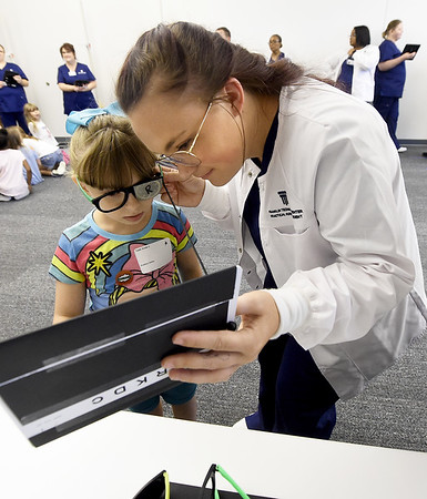 Kansas City University student Breeanna Tucker performs a vision test on Brooklyn Danley, 7, during KCU's Score 1 for Health event on Tuesday at KCU. The children's preventative screening program involved about 130 West Central Elementary students and included basic health screenings and educational presentations for the kids.<br /> Globe | Laurie Sisk