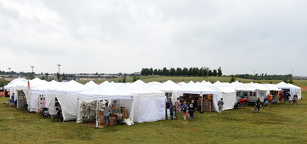 A small village of tents protects visitors, artists and their works from rain during the Joplin Arts Fest on Saturday at Mercy Park.<br /> Globe   Laurie Sisk