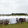 A small village of tents protects visitors, artists and their works from rain during the Joplin Arts Fest on Saturday at Mercy Park.<br /> Globe | Laurie Sisk