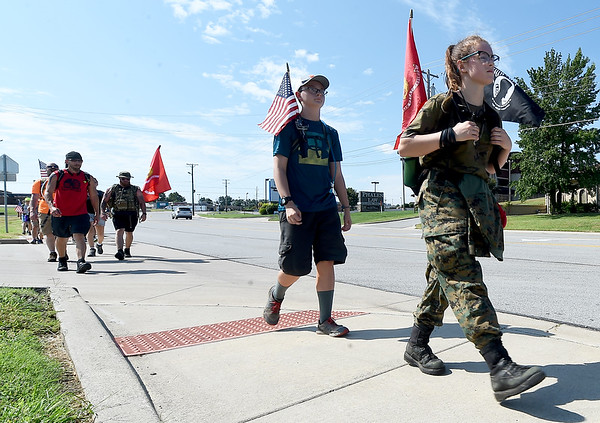 """Allison Robbins, 15, right, and Josiah Starr, 12 of Carl Junction Scout Troop 70, make their way up McClellansd Blvd. during the """"Let's Roll '19 Ruck March"""" on Saturday. The event, sponsored by Compass Quest, included about 30 participants who hiked the 14-mile course to raise awareness concerning veteran's issues.<br /> Globe   Laurie Sisk"""