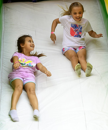 From the left: Buddies Brileigh Boyer, 7 and Hadley Hant, 7, both of Pittsburg, enjoy a trip down an inflatable slide during the Carl Junction Bluegrass Festival on Saturday at Center Creek Park. <br /> Globe | Laurie Sisk