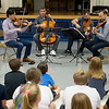 (from left) Members of the Miro Quartet Daniel Ching, Joshua Gindele, John Largess and William Fedkenheuer play for students at Cecil Floyd Elementary on Wednesday.<br /> Globe | Roger Nomer