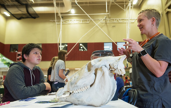 Brandy Blanton, a vet tech instructor at Crowder College, talks with Levi King, Joplin High freshman, about veterinarian science during Thursday's Ag Day at Joplin High School.<br /> Globe | Roger Nomer