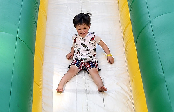 Four-year-old Ben Cullumber enjoys a trip down an inflatable slide courtesy of the Missouri Southern Athletic Department during Third Thursday on Thursday in downtown Joplin.<br /> Globe | Laurie Sisk