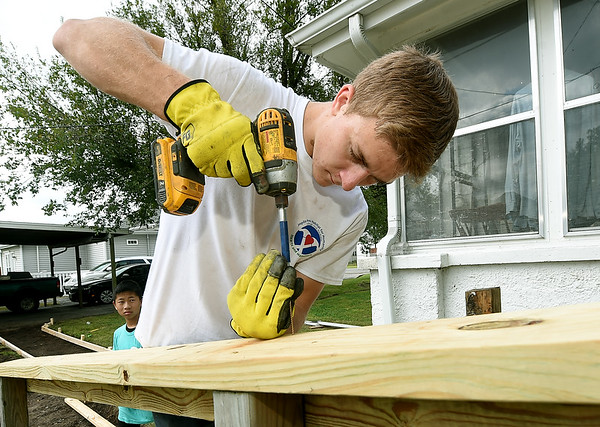 Corbin Bandy helps install handrails on a ramp at a Webb City home on Main Street on Saturday. About 155 volunteers from God's Resort, Hearts & Hammers and Joplin Area Habitat for Humanity tackled 22 projects as part of a Brush With Kindness event.<br /> Globe | Laurie Sisk