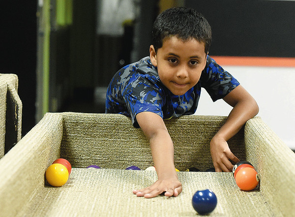 Nine-year-old Junior Shepherd plays a game of carpet ball on Tuesday afternoon at the Boys and Girls Club of Southwest Missouri.<br /> Globe | Laurie Sisk