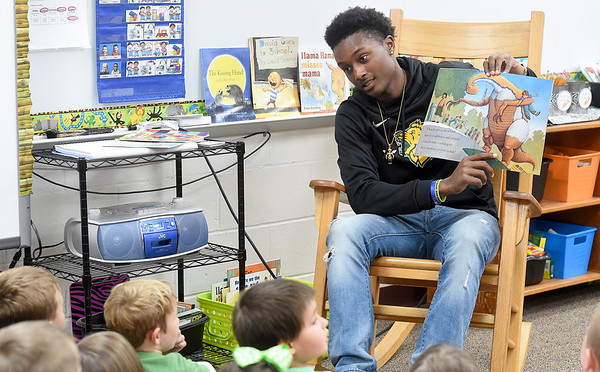 """Missouri Southern basketball player Winston Dessesow reads the book """"How Do Dinosaurs Go to School?"""" to kindergartners at Cecil Floyd Elementary on Thursday morning. Dessesow was one of three MSSU players to read to kids at the school.<br /> Globe   Laurie Sisk"""