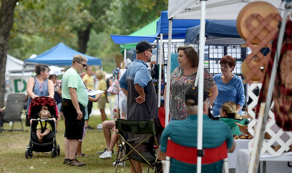 Shoppers check out the vendors offerings during the Carl Junction Bluegrass Festival on Saturday at Center Creek Park. <br /> Globe | Laurie Sisk